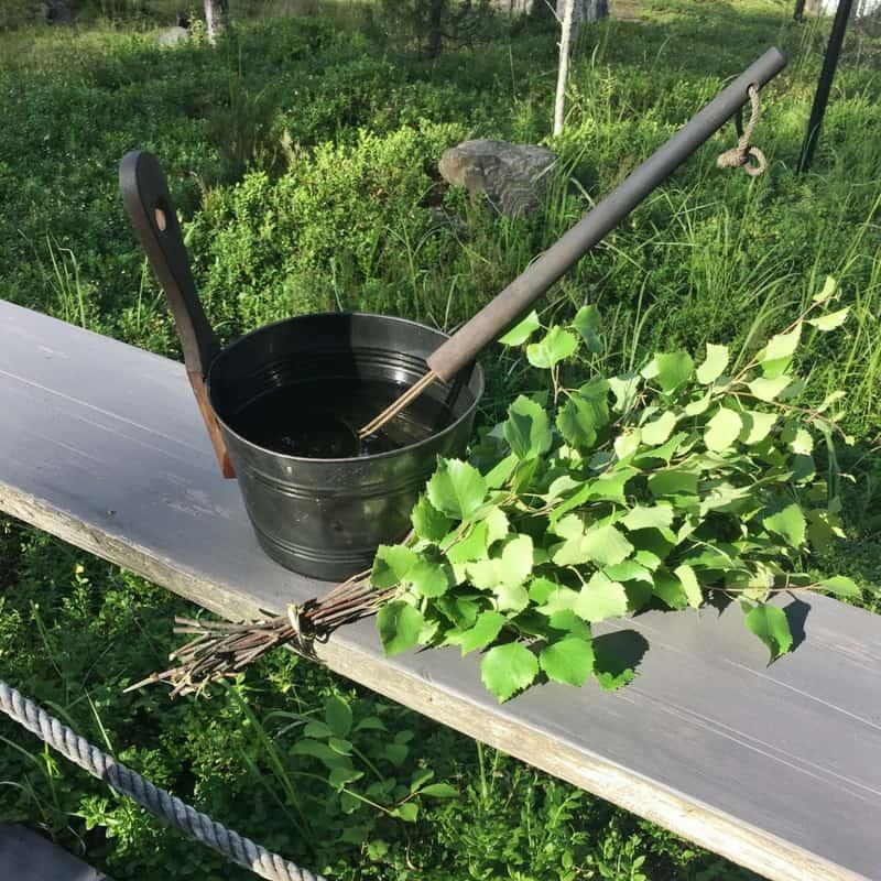 Finnish sauna bucket filled with water and birch branches