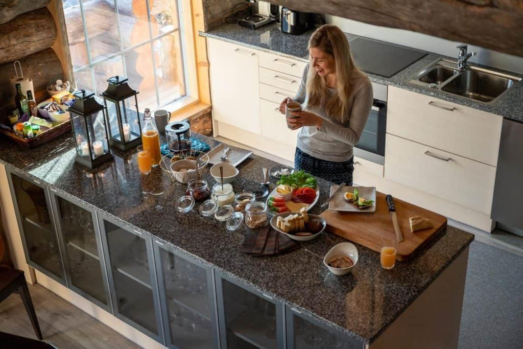 Woman standing in kitchen in front of breakfast dishes and foods on the counter
