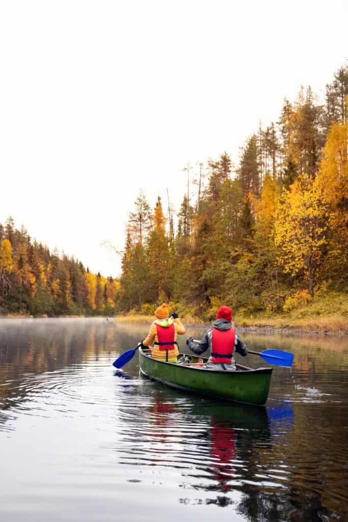 2 people canoeing through the river between 2 forests