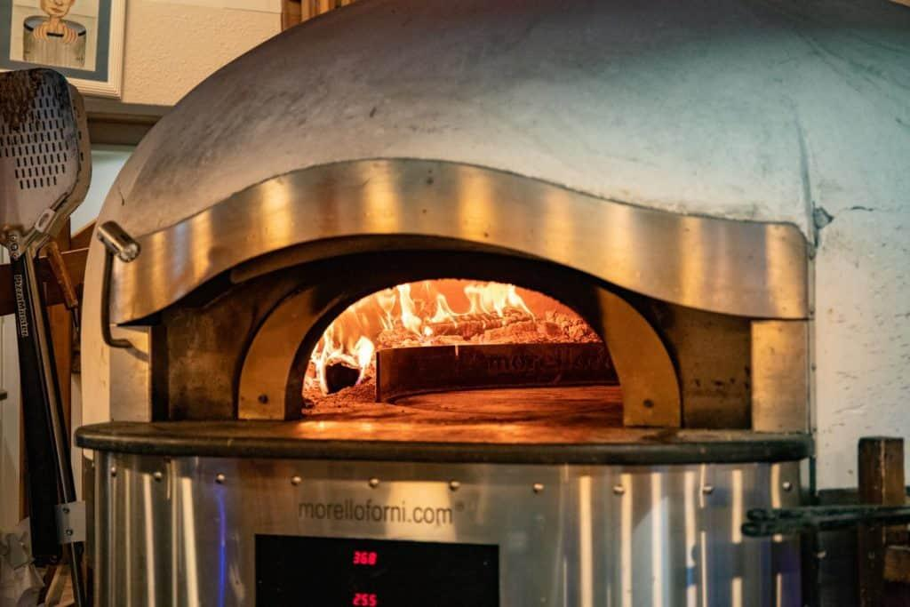 brick fire pizza oven with flames inside