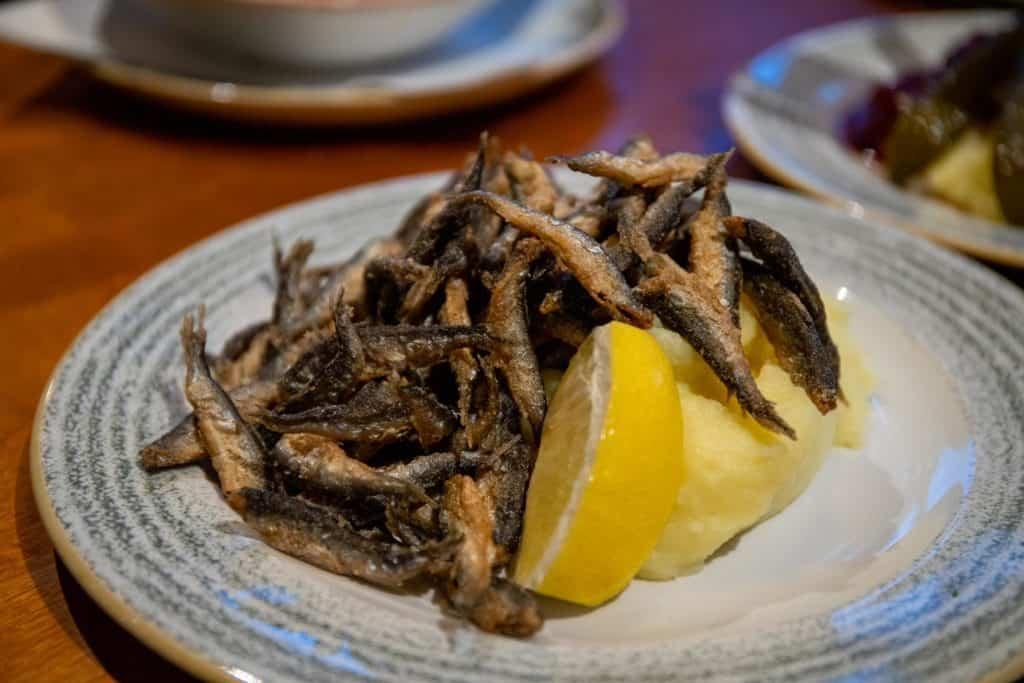 small fried vendace fish on top of mashed potatoes on a plate